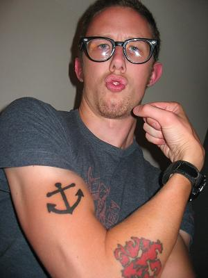 Black Ink Anchor Tattoo On Biceps