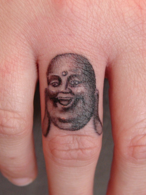 Buddha Face Tattoo On Finger