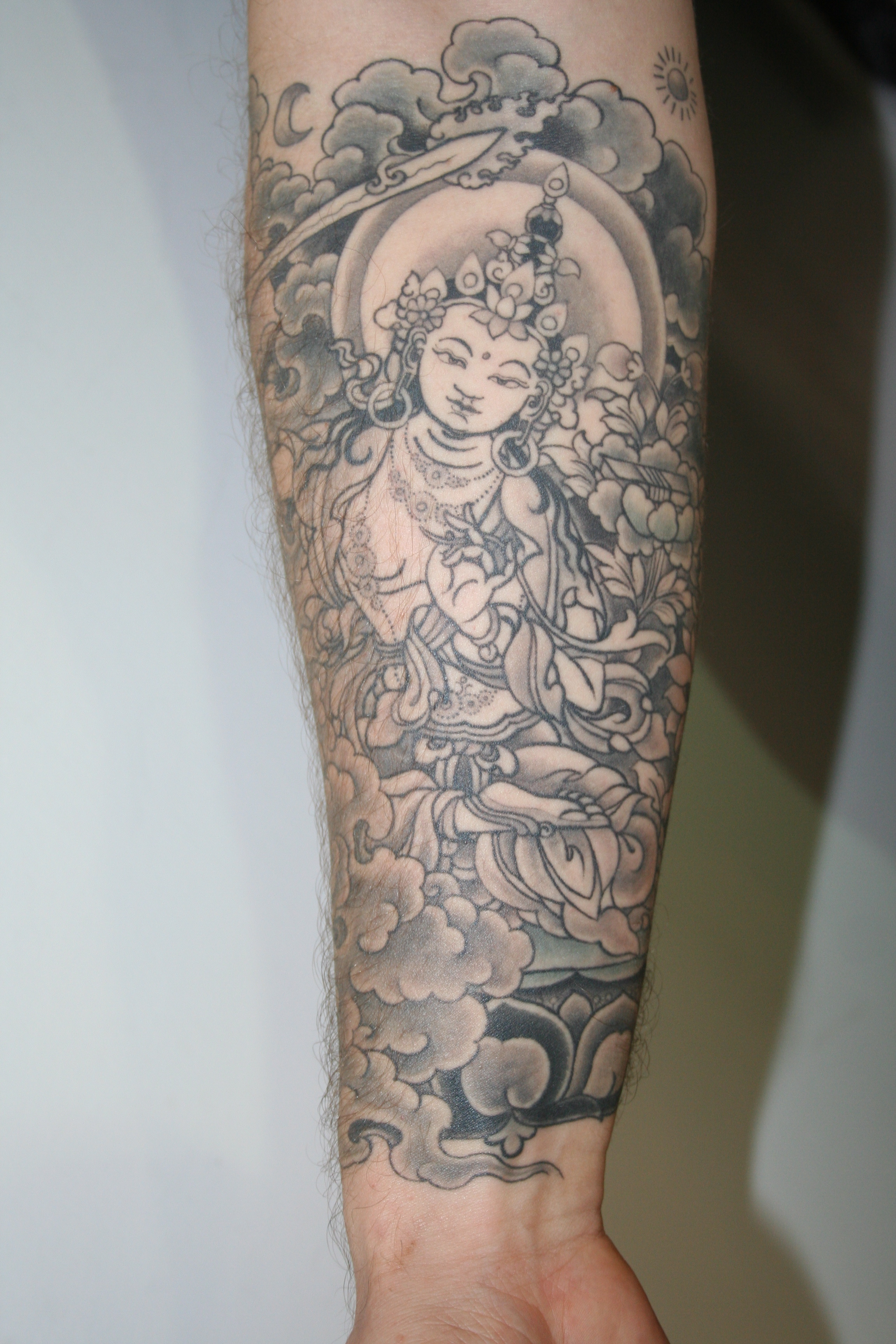 Grey Ink Buddhist Tattoo On Forearm