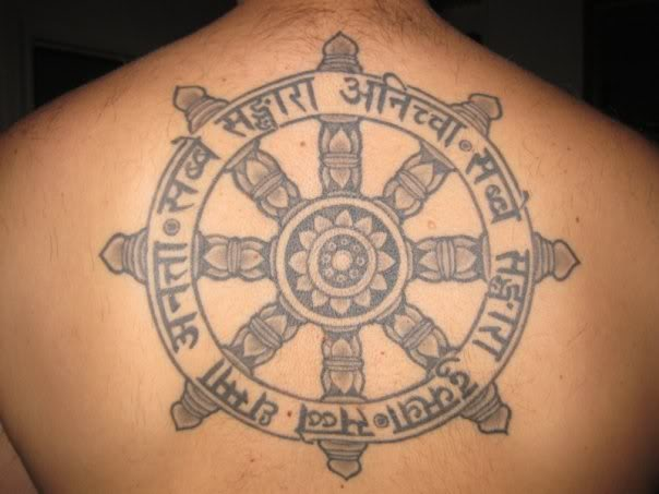 Grey Ink Buddhist Wheel Tattoo On Upper Back