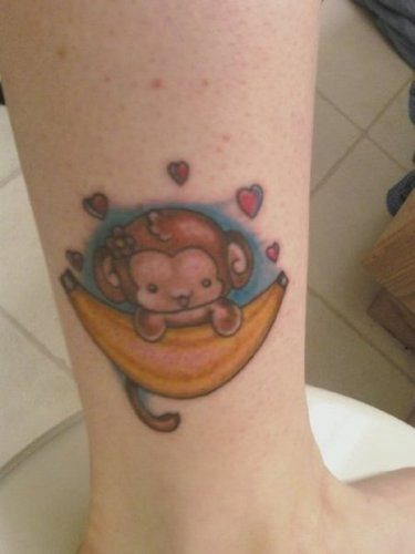Cartoon Monkey On Banana Tattoo