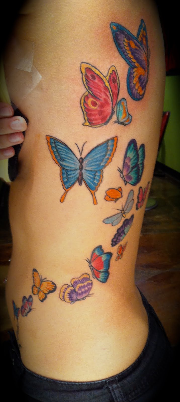 http://www.tattoobite.com/wp-content/uploads/2013/10/colorful-butterflies-tattoo-on-rib-side.jpg