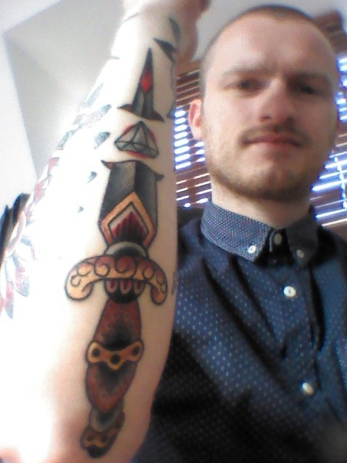 Guy Showing Dagger Tattoo Design On Arm