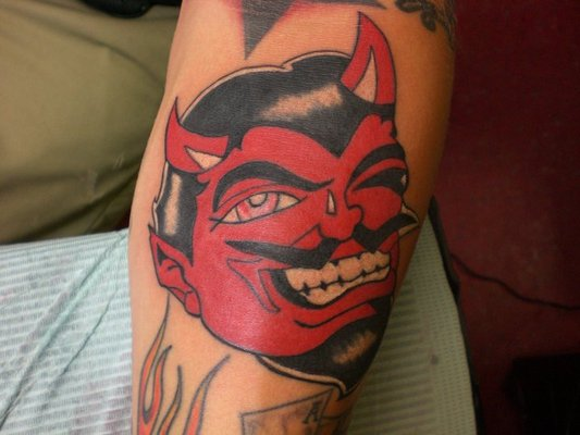Red Ink Devil Face Tattoo On Arm