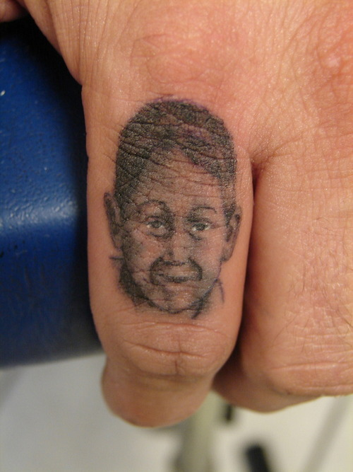 Baby Face Portrait Tattoo On Finger