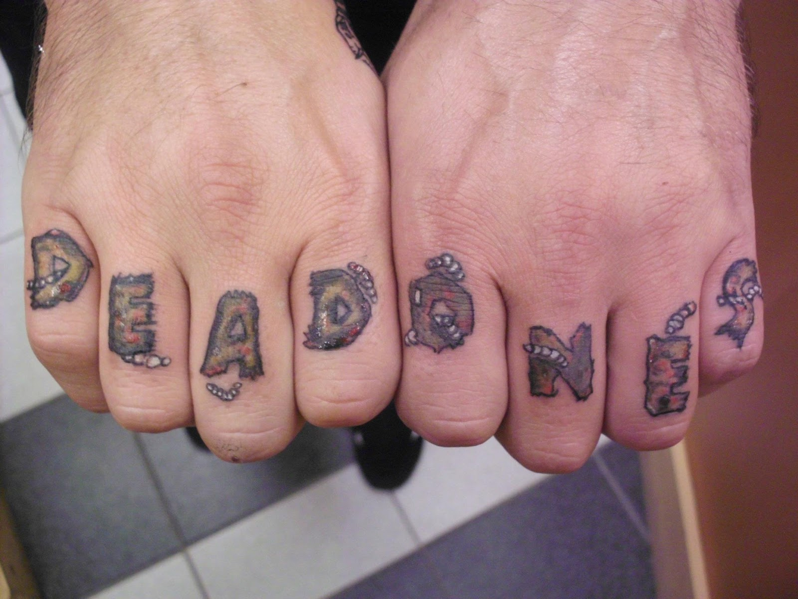 Dead Ones Tattoo On Fingers