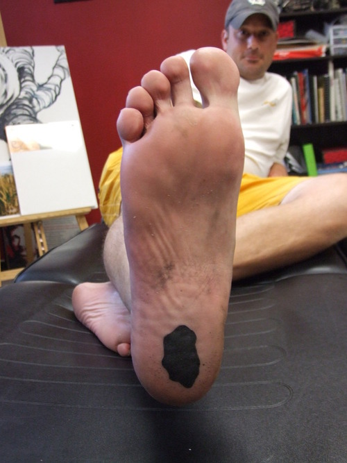 Black Ink Tattoo On Back Of Heel