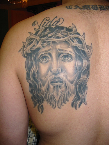 Grey Ink Jesus Portrait Tattoo On Back Shoulder