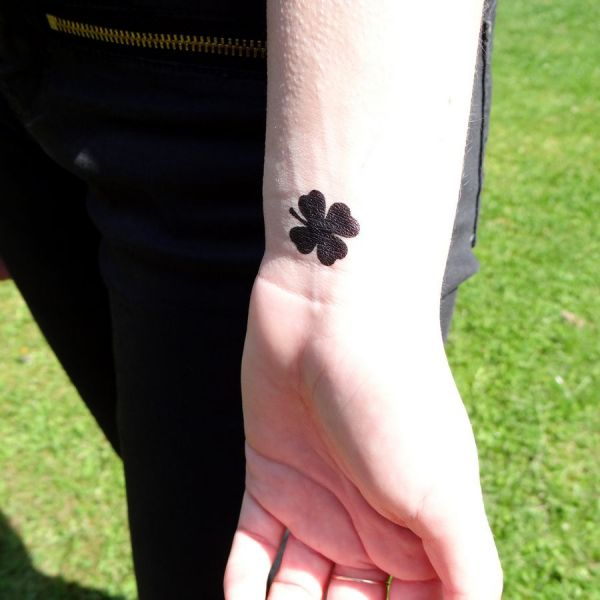 Black Ink Four Leaf Clover Tattoo On Wrist