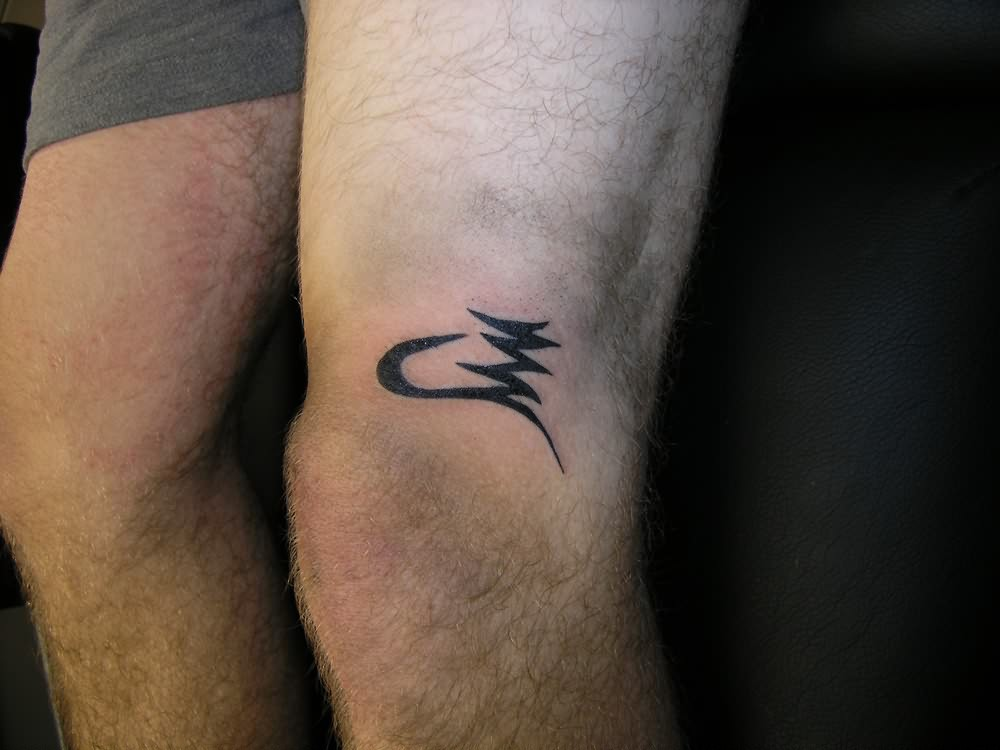 Black Ink Symbol Tattoo On Knee