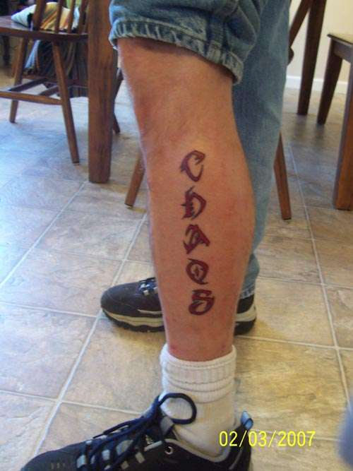 Chaos Tribal Lettering Tattoo On Leg