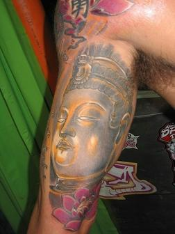 A Buddha & Lotus Flower Tattoo On Muscles