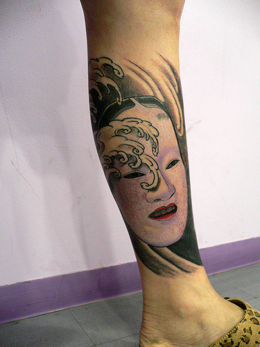 Japanese Mask Tattoo On Lower Leg