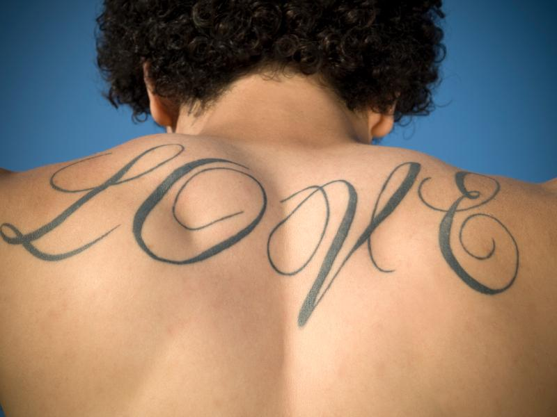 Love Word Tattoo On Upper Back
