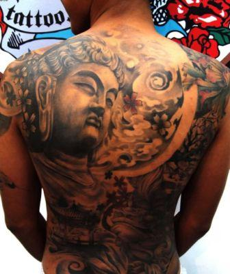 Grey Ink Buddhist Tattoo On Back Of Shoulder