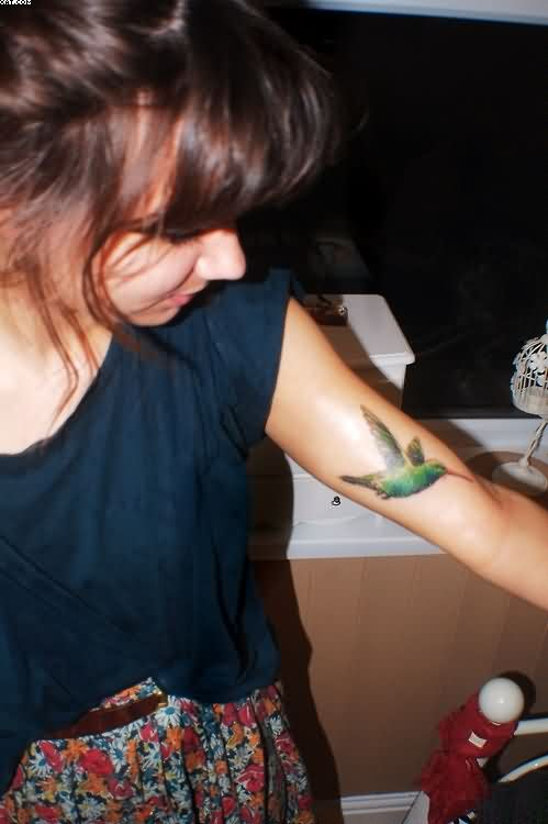 Small Green Hummingbird Tattoo On Arm Of Girl