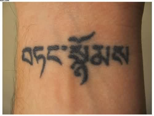 Black Ink Buddhist Tattoo On Wrist