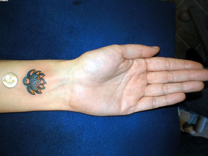 Cute Lotus Tattoo On Wrist And A Coin