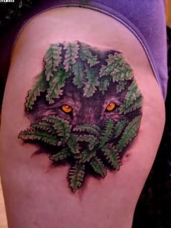 Wolf Eyes Among Green Leaves Tattoo On Thigh