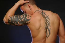Black Ink Tribal Tattoos On Left Arm And Back
