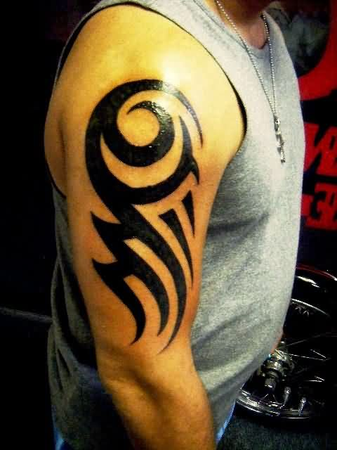 Glowing Black Ink Tribal Tattoo On Biceps