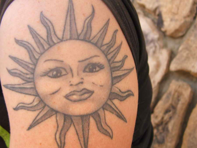 Grey Ink Sun Face Tattoo On Shoulder