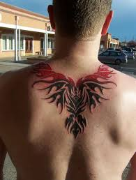 Red And Black Ink Tribal Phoenix Tattoo On Upper Back