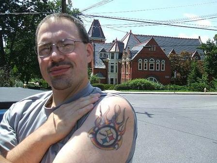Man Showing Flaming Sports Logo Tattoo On Shoulder