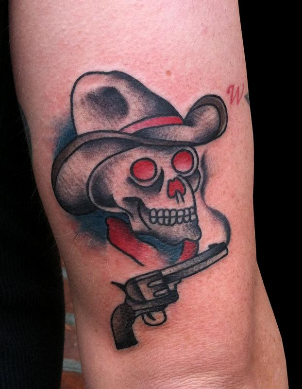 A Traditional Cowboy Skull And Revolver Tattoo