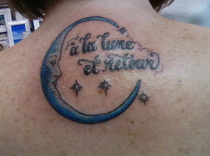 Blue Face Moon And Wording Tattoos On Back Neck