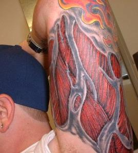 Flames And Ripped Skin Tattoos On Arm