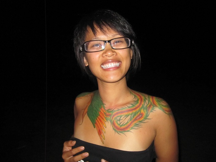 Girl Showing Teeth And Colorful Neck Tattoos