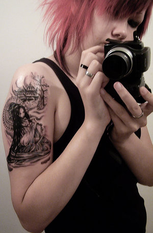 Girl With Black Camera And Right Shoulder Tattoo