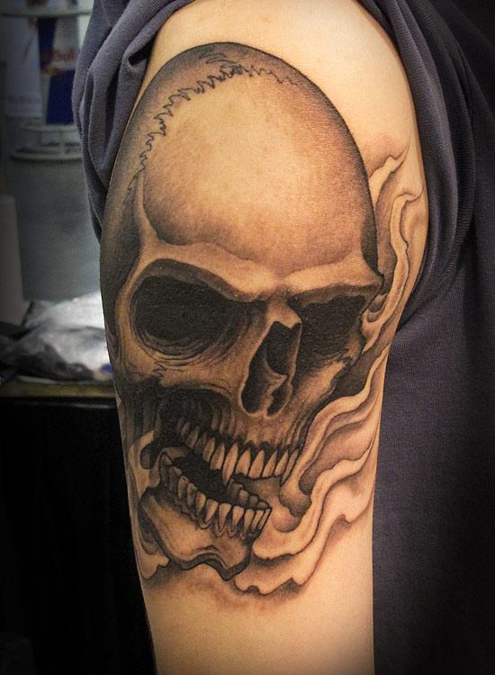 Grey Ink Skull And Flame Tattoos On Biceps