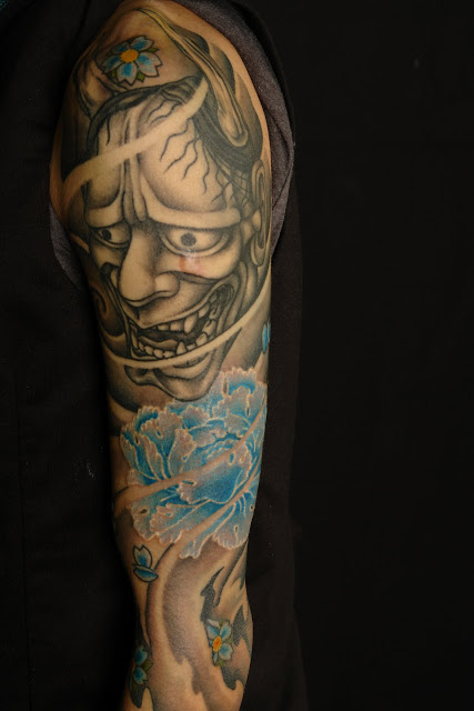 Japanese Mask And Blue Flower Tattoos On Sleeve