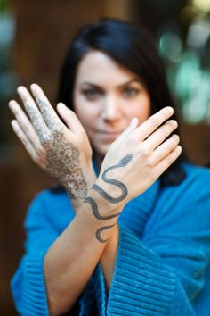 Lady Showing Henna And Snake Hand Tattoos