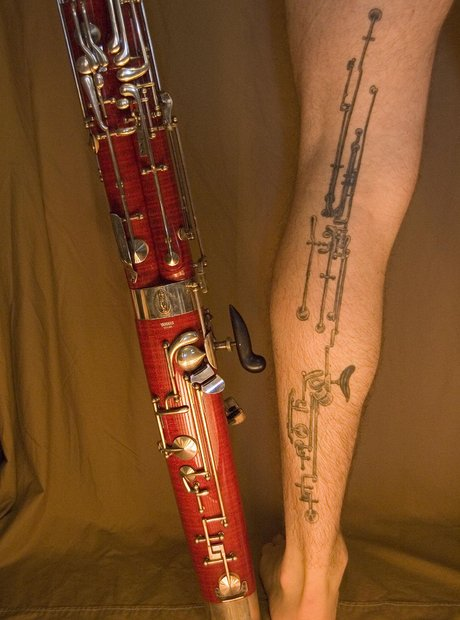 Long Music Instrument Tattoo On Back Leg