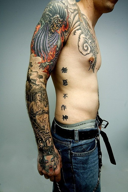 Asian Tattoos On Right Arm And Ribs