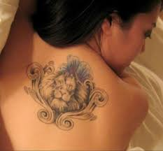 Blue Flower And A Leo Symbol Tattoo On Upperback