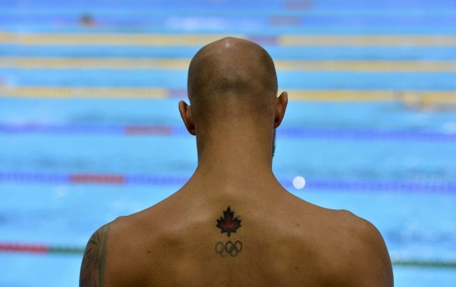 Canadian Leaf And Olympic Logo Tattoo On Upperback