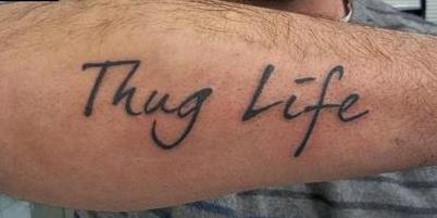 Clear Thug Life Tattoo On Arm