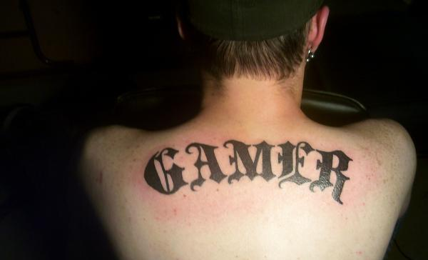 Dark Black Ink Gamer Tattoo On Upperback