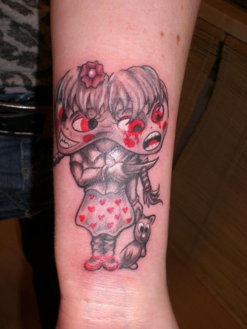 Double Headed Wicked Girl Tattoo On Lower Arm