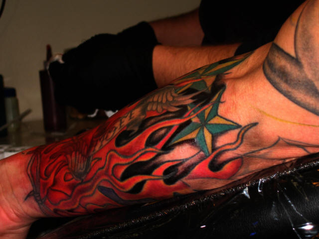 Flames And Nautical Star Tattoos On Arm