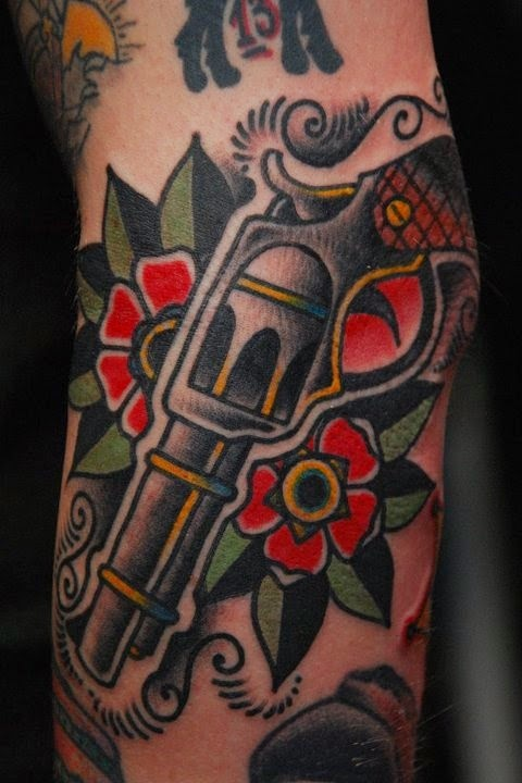 Flowers With Pistol Tattoos On Arm