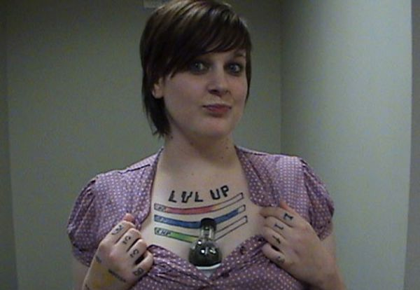 Girl Showing Bad Video Game Tattoo On Chest