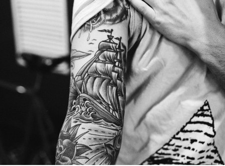 Grey Nautical And Rose Tattoos On Sleeve