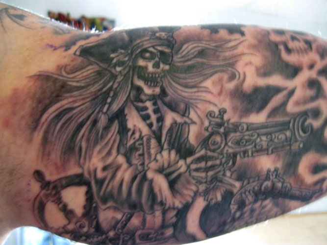 Grey Pirate Skeleton With Pistol Tattoos On Muscles