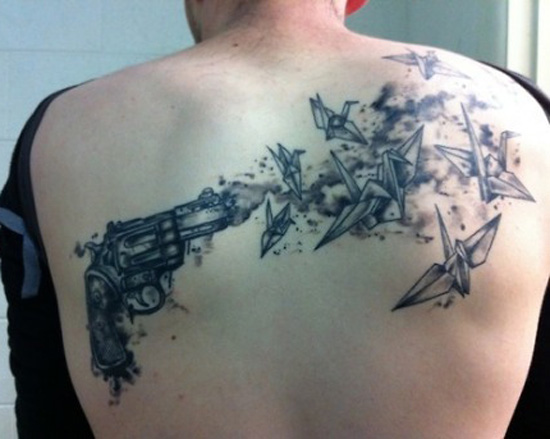 Grey Pistol And Paper Crane Tattoos On Back