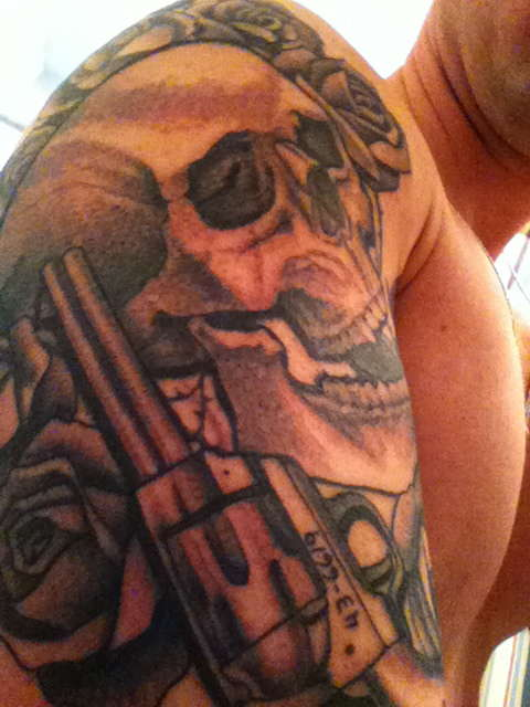 Grey Roses Skull And Pistol Tattoos On Upper Arm